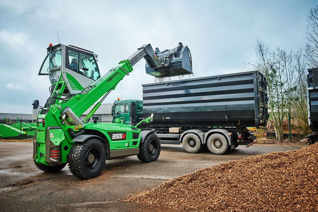 Robust telescopic handler for the waste recycling industry with elevating driver's cab: the SENNEBOGEN 355 E – an ideal alternative to the wheel loader: Wood chip loading